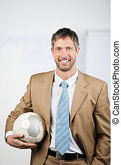 Businessman Holding Soccer Ball In Office