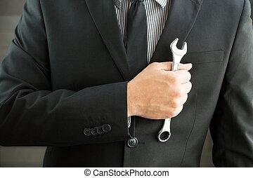 Businessman holding spanner in hand