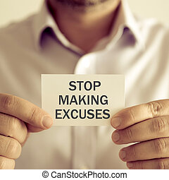 Businessman holding STOP MAKING EXCUSES message card