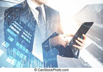 Businessman holding tablet and digital falling chart hologram