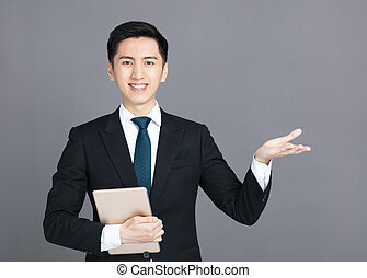 Businessman holding tablet and presenting something in hand