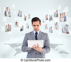 Businessman holding tablet encircled by digital interface of...