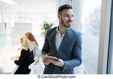 Businessman holding tablet in modern office