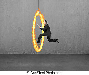 Businessman holding tablet jumping through fire hoop with concre