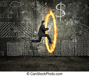 Businessman holding tablet jumping through fire hoop with doodle