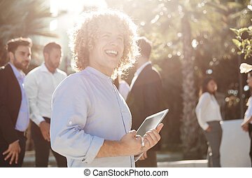 Businessman holding tablet outside laughing