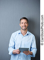 Businessman Holding Tablet PC Against Blue Wall