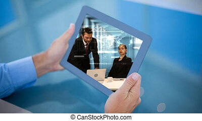 Businessman holding tablet showing busiesspeople video