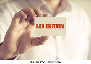 Businessman holding TAX REFORM message card - Closeup on ...