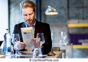 Businessman holding the menu in a restaurant