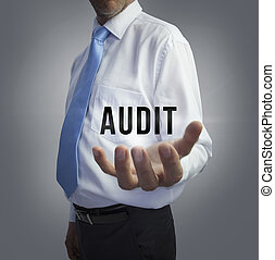 Businessman holding the word audit on grey background
