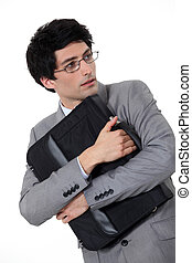 businessman holding tight his briefcase