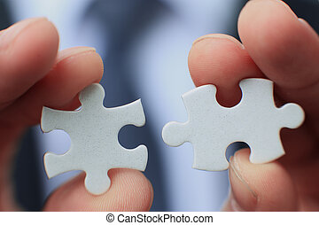 Businessman holding two blank white puzzle pieces in his...