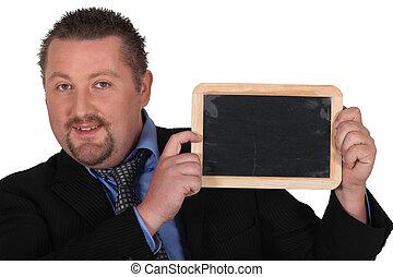 Businessman holding up a chalkboard