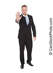 Businessman holding up his hand in a stop gesture