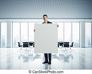 Businessman holding white canvas at contemporary office