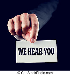 We hear you - Businessman holding white card with We hear...