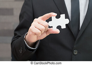 Businessman holding white jigsaw piece, New vision concept