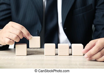 Businessman holding wooden cube in his hand