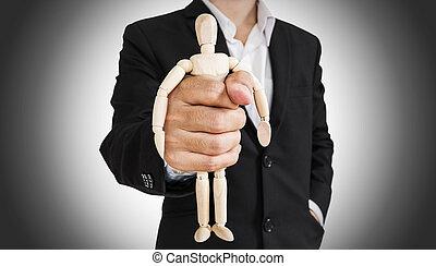 Businessman holding wooden figure