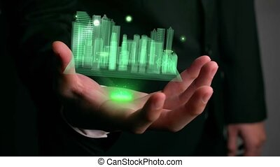 Businessman holds 3D city model showing augmented reality technology . Futuristic urban hologram screen in concept of virtual internet of things and global network connection .