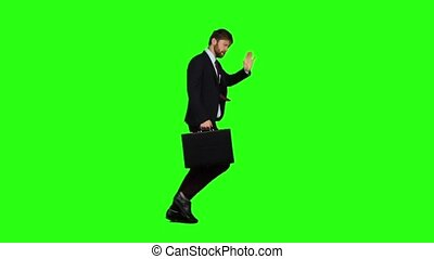 Businessman holds a briefcase in his hand, he rushes over it. Green screen. Slow motion