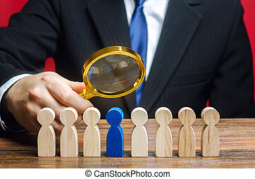 Businessman holds a magnifying glass over a worker. Recruitment concept. Hiring, hire. The best employee, leader. Leadership and promotion. Human Resource Management. Toxicity in the team.