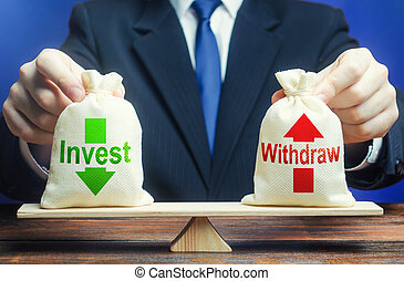 Businessman holds bags Invest and Withdraw on scales. ...
