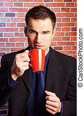 Businessman holds cup of coffee