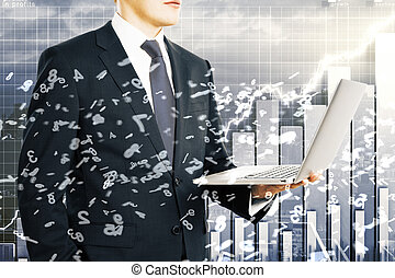 Businessman holds laptop with flying numbers at business chart background