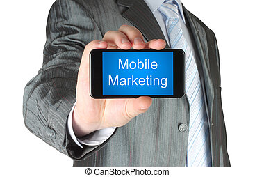 Businessman holds smart phone with mobile marketing words on its screen isolated on white background.