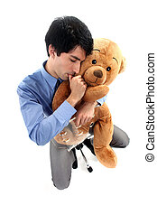 Businessman hugging teddy bear and sucking thumb