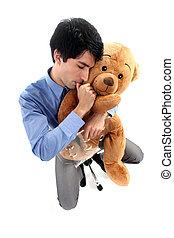 Businessman hugging teddy bear and sucking thumb