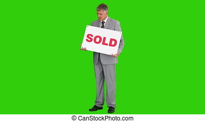 Businessman in a a gray suit with a sold sign - Chroma-key...