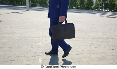 Businessman in a blue suit walks down the street. Slow motion