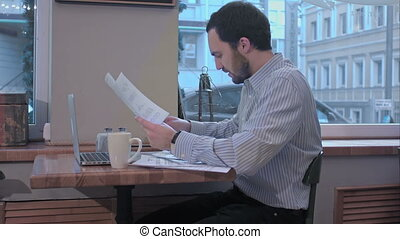 Businessman in a cafe reading with interest a contract document.