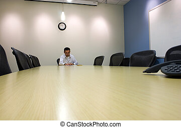 Businessman looking over his galsses in a Conference Room