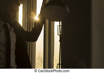 Businessman in a dark office with sunburst