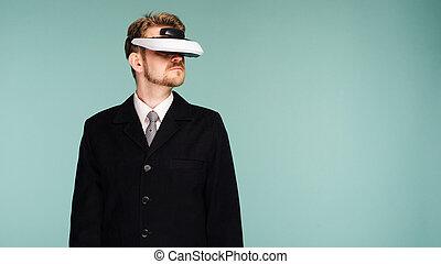 Businessman in a formal wear wearing virtual reality glasses...