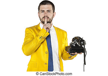 businessman in a gold suit holding the telephone and asks for silence