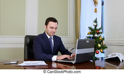 Businessman in a good mood working on laptop computer in the office