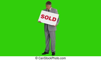 Businessman in a gray suit with a sold sign - Chromakey...