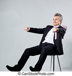 businessman in a luxury suit is riding on an imaginary motorcycle