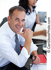 Businessman in a meeting smiling at the camera