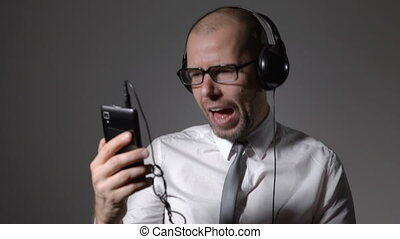 Businessman in a shirt and big headphones, singing in a smartphone, uses an application.