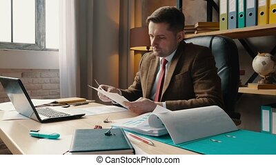 A businessman in a suit analyzes a business plan and a report with graphs about the level of sales.