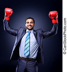 Businessman in a suit and boxing gloves, celebrating a win,...