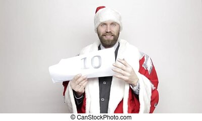 businessman in a suit of Santa Claus holds a sheet of paper...