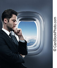businessman in airplane - thinking businessman standing in...