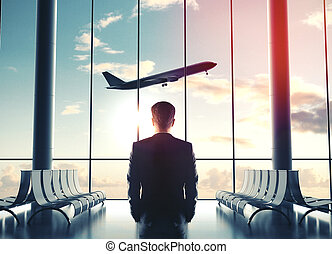 Businessman in airport and looking at airplane